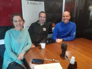Paula Cunniffe, John O'Regan and Mark Pollock sitting at a table smiling at the camera with a whiteboard with training tips written on it behind them